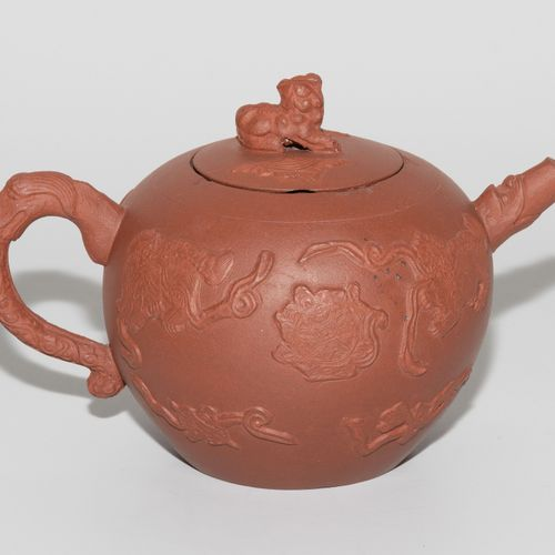 Teekanne 茶壶  中国。宜兴陶器。棕红色的身体上有护卫狮子的浮雕,玩弄着彩带。盖子上有雕刻的护卫狮子作为把手。高10厘米。 略有磨损。