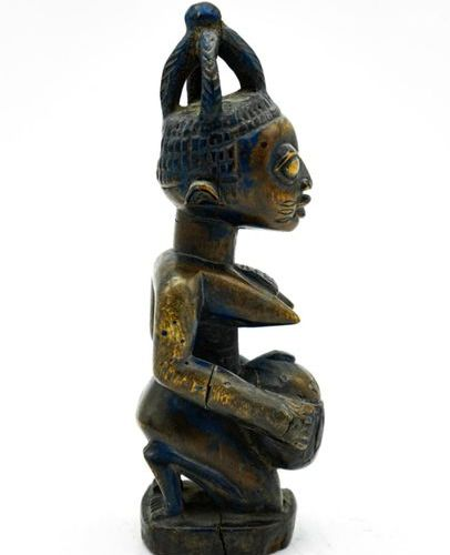 Yoruba statuette Nigeria Wood, pigments H.: 22 cm. Female figure kneeling on a c…