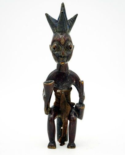 Yoruba statuette Nigeria Wood, pigments H.: 24.5 cm. A seated male figure with c…