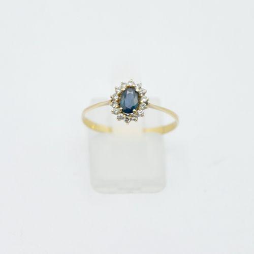 Bague en or 750/1000e centrée d'une pierre bleue entourage de petits diamants  P…