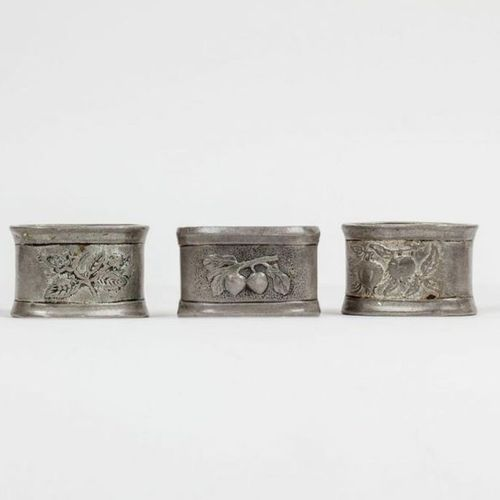 Suite of three pewter napkin rings with fruit and flower decorations. Different …