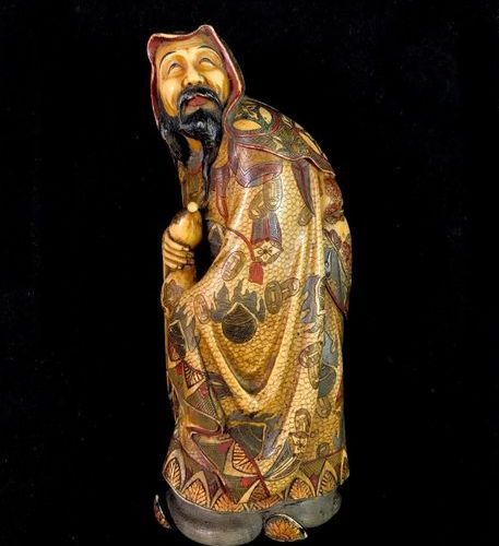 A polychrome ivory okimono representing a Chinese sage holding a gourd, dressed …