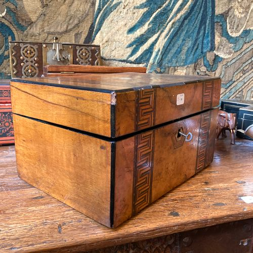 A walnut veneered compartmentalized box, decorated with a frieze of inlaid greek…