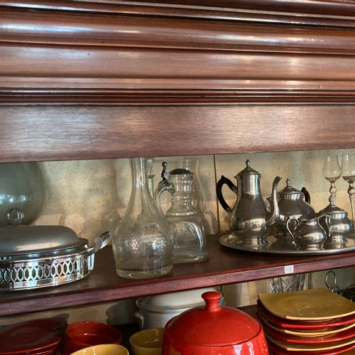 Contents of the first shelf: punch bowl, pewter tea and coffee set, a pitcher, t…