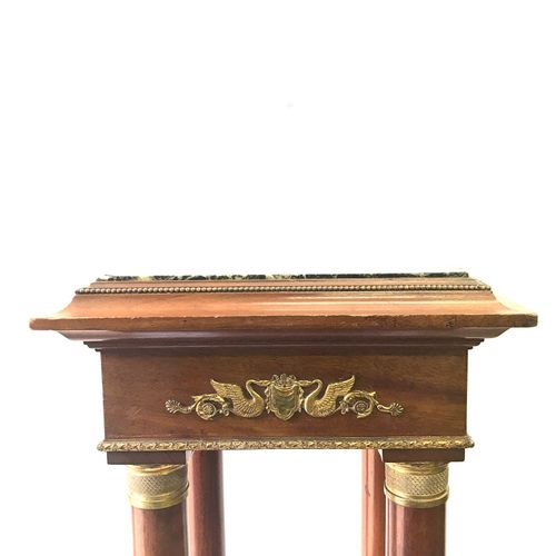 Square base sellette resting on four round legs supporting four mahogany columns…