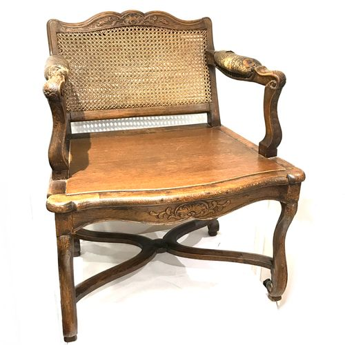 Low armchair in cabriolet, in stained walnut, moulded and carved. It rests on fo…