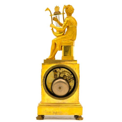 A Empire Period Pendule fire gilded, Empire period, ca.1810, with god playing ly…