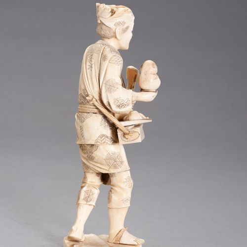AN IVORY AND BONE OKIMONO OF A TOY SELLER AN IVORY AND BONE OKIMONO OF A TOY SEL…