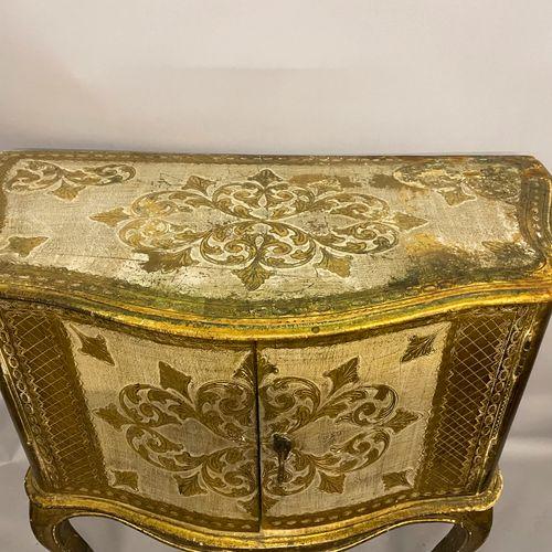 COMMODE galbée en bois doré et blanc à décor gravé de feuilles et rinceaux. Elle…