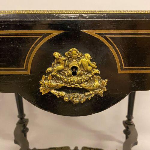 TABLE en bois noirci à décor en laiton doré d'attributs de musique dans une guir…