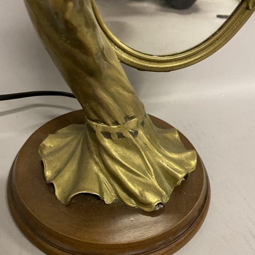 LAMPE en laiton doré à décor d'une jeune femme tenant un miroir de forme ovale, …