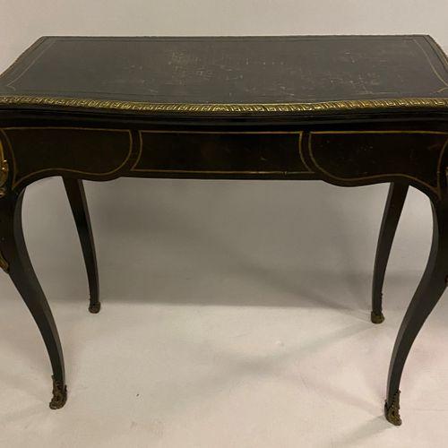 TABLE A JEUX en bois noirci marqueté de cubes et filets de laiton dorée. Elle re…