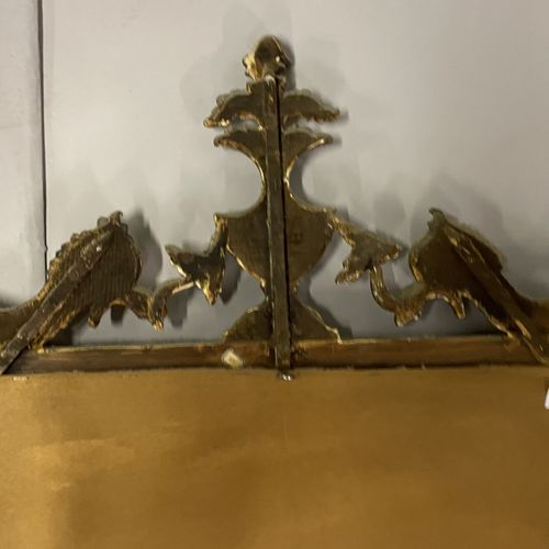 MIROIR en bois laqué vert et doré surmonté d'un vase flanqué de deux poissons MI…