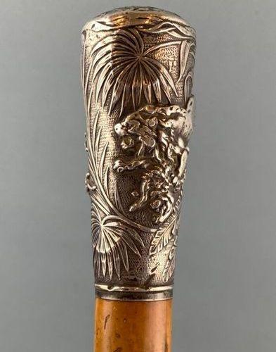 Canne de marche, pommeau en argent figurant un lion poursuivant ses proies dans …