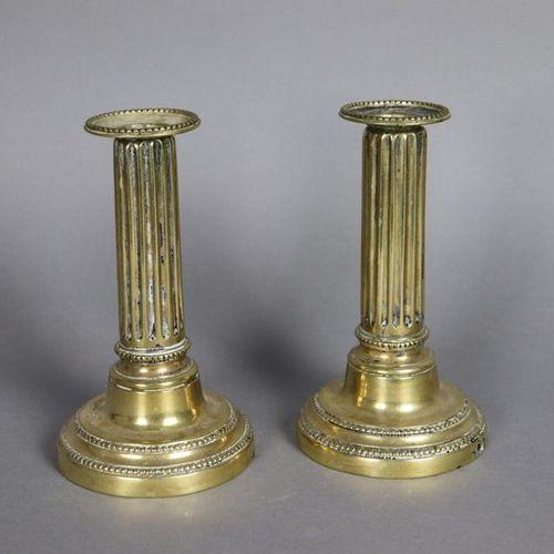 Paire de bougeoirs en bronze doré à décor de filets de perles et cannelures sur …