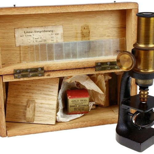 Cast iron and brass microscope with accessories in oak case, Germany, interbellu…
