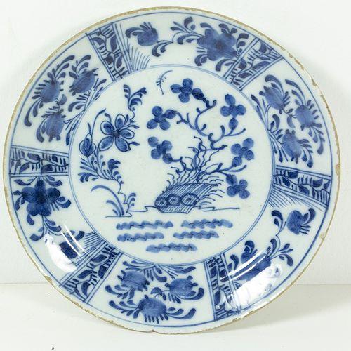 Porcelaine, faïence, etc. Une assiette en faïence de Hollande à décor central de…