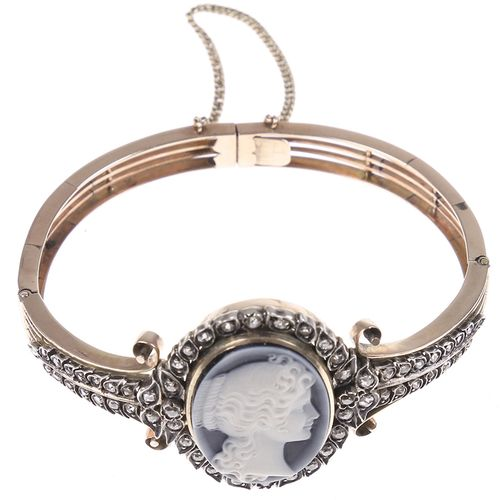 Gold jewellery and objects 14k hinged bangle bracelet set with a cameo depicting…