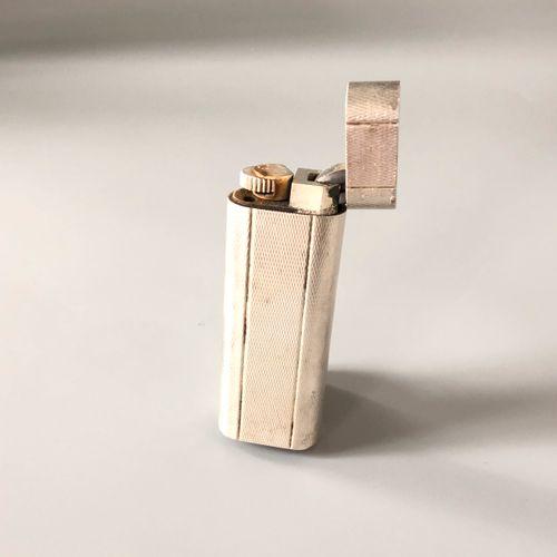 CARTIER 镀银金属打火机,长方形,有十字架和神像的装饰。燃气加注。有签名和编号的。在其案件中。( 小型磨损)。 尺寸:2,7 x 7 x 1,2厘米左右。