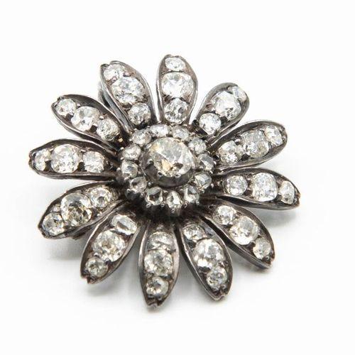 A VICTORIAN DIAMOND SET PENDANT BROOCH, the flower head mount with twelve petals…