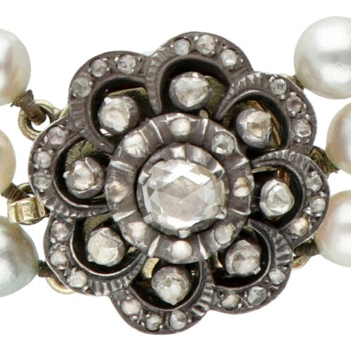 Three row freshwater pearl necklace with a 14K. Yellow gold/silver flower shaped…