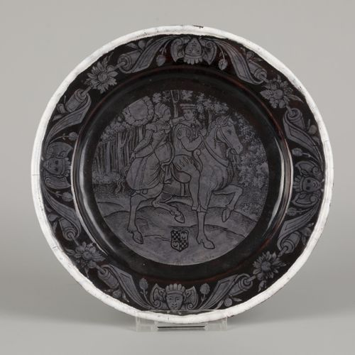 A black and grey enamelled charger depicting an equestrian couple, France, ca. 1…
