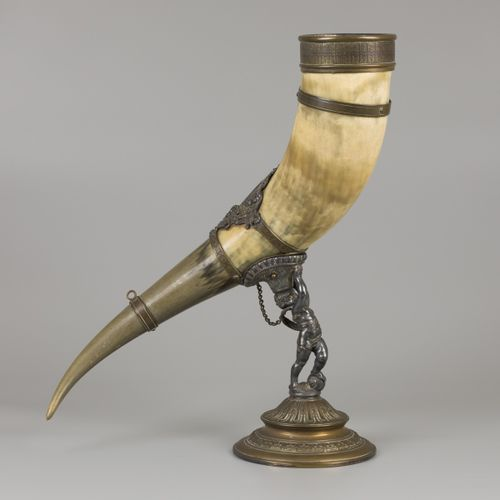 A drinking horn made of an ox horn, carried by a putto, ca. 1920. Estimation : €…
