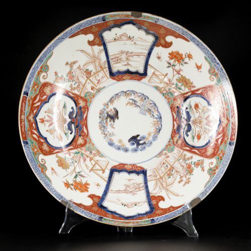 A large Imari dish with floral decoration and landscapes on the outside. Japan, …