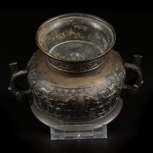 A bronze incense burner, China, 19th century. 两个拟人化的把手,汉藏语系的图案,背景是雕刻的蜿蜒曲折,下面有汉字标…
