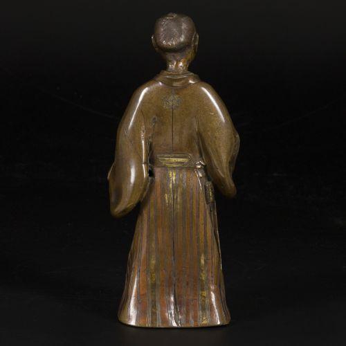 A bronze courtir, Japan, late Meji. Dim. 28 x 12 cm. Estimation : 80 € 120 €.