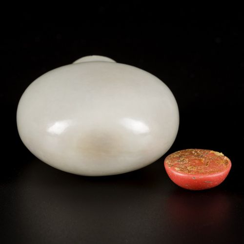 A celadon jade snuff bottle with blood coral cap, China, 19th century. H. 6 cm. …