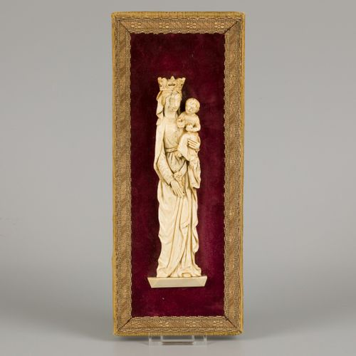 An ivory relief of a standing Madonna with lily mount on red velvet background, …