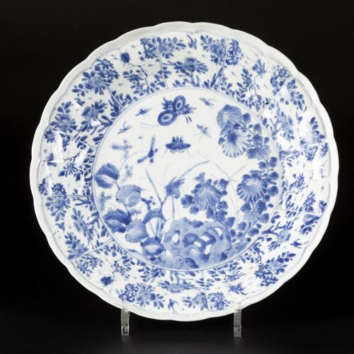 A porcelain charger with floral decoration in sections, with a central decoratio…