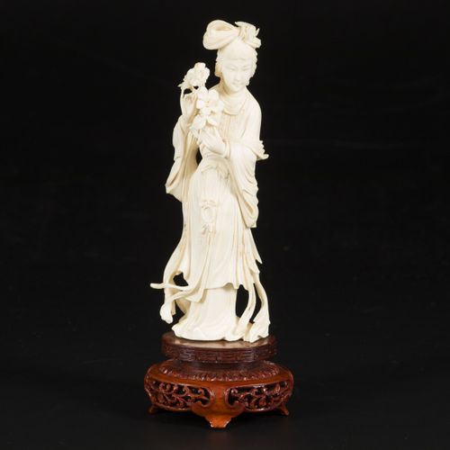 An ivory Guanyin on a wooden base, China, early 20th century. Dim. 21 x 7 cm. Es…