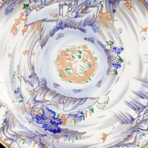 A large porcelain charger with dragon decor in the centre, surrounded by a river…