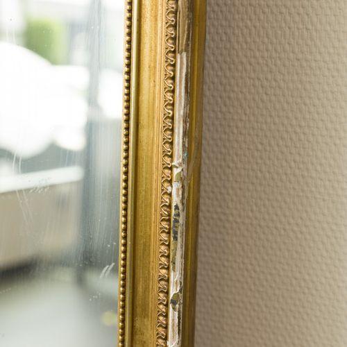 A monumental mirror, France, 20th century. Couronné de motifs de feuilles, cadre…