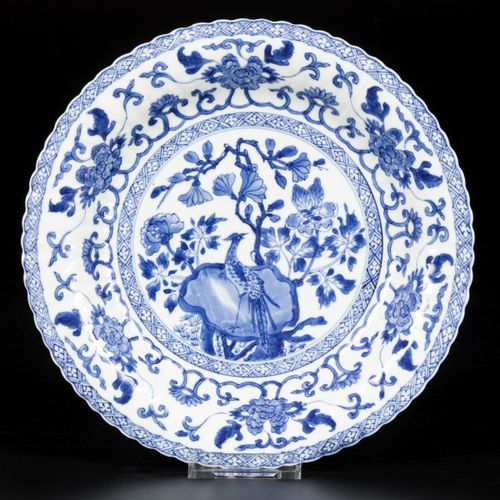 A ribbed porcelain plate with decor of bird on rock, China, Kangxi. 直径24厘米。毛边。估计…