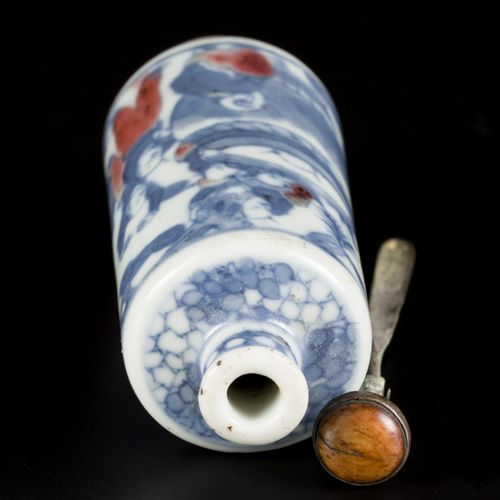 A porcelain iron red snuff bottle decorated with playing kids around a fish bowl…