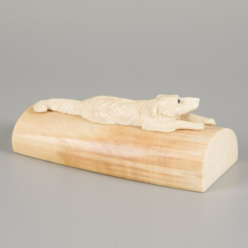 An ivory presse papier with carved reclining dog, 1st half 20th century. 有玻璃眼珠(一…