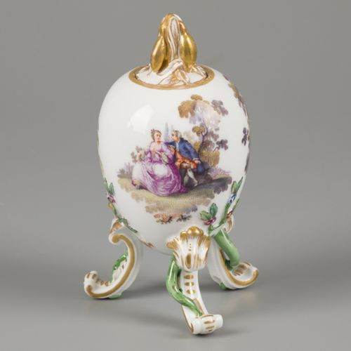 A porcelain egg on legs and a leaf shaped knob, decorated with classical scenes …