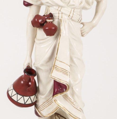 An earthenware sculpture of a man carrying a jug. Royal Dux, 1st half 20th centu…
