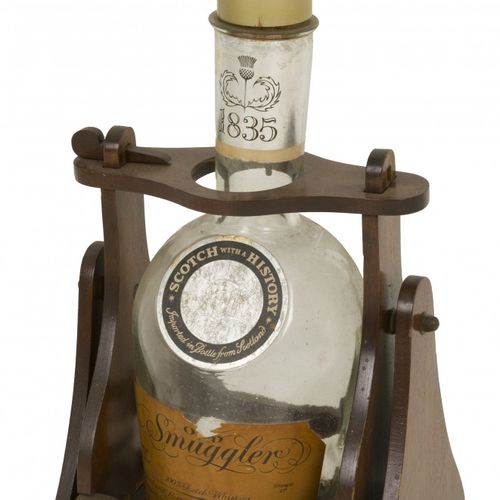 """An """"Old Smuggles"""" Scotch Whisky bottle in holder, 20th century. 成立时间:1835年,原始内容。…"""