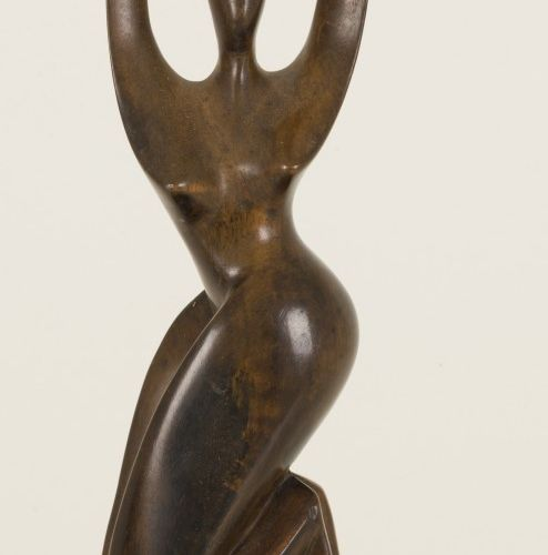 A carved wooden sculpture of a kneeling dancer mounted on a brass base, 20th cen…