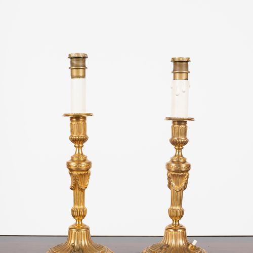 From a prestigious Parisian Palace Pair of chased and gilded bronze torches, the…