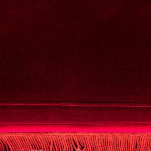 Un canapé trois places en velours rouge, à franges. Avec trois coussins.  H : 92…