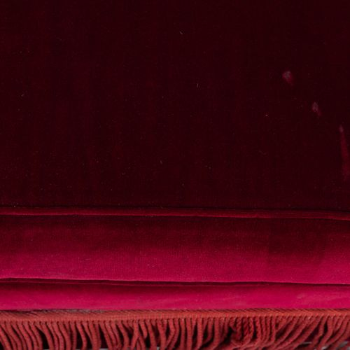Un canapé deux places en velours rouge, à franges. Avec deux coussins.  H : 92 c…