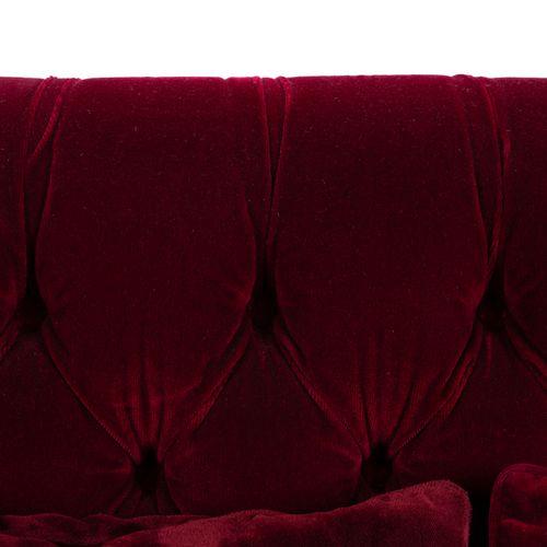 Un canapé trois places en velours rouge, à dossier capitonné et à franges. Avec …