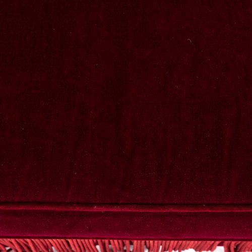 Un canapé convertible deux places en velours rouge, à franges. Avec un coussin. …