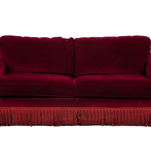 Un canapé convertible deux places en velours rouge, à franges.  H : 85 cm L : 19…