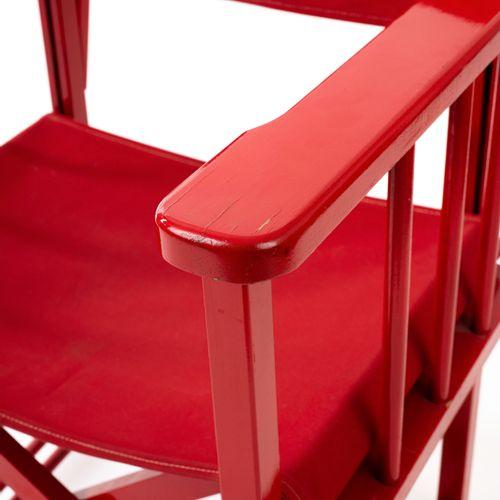 En provenance de l'ancien siège de GUERLAIN Un fauteuil en bois laqué rouge, ass…